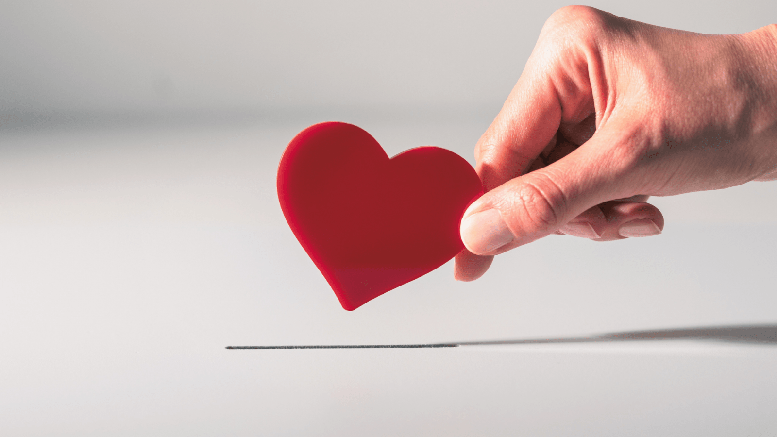 hand putting red heart into box