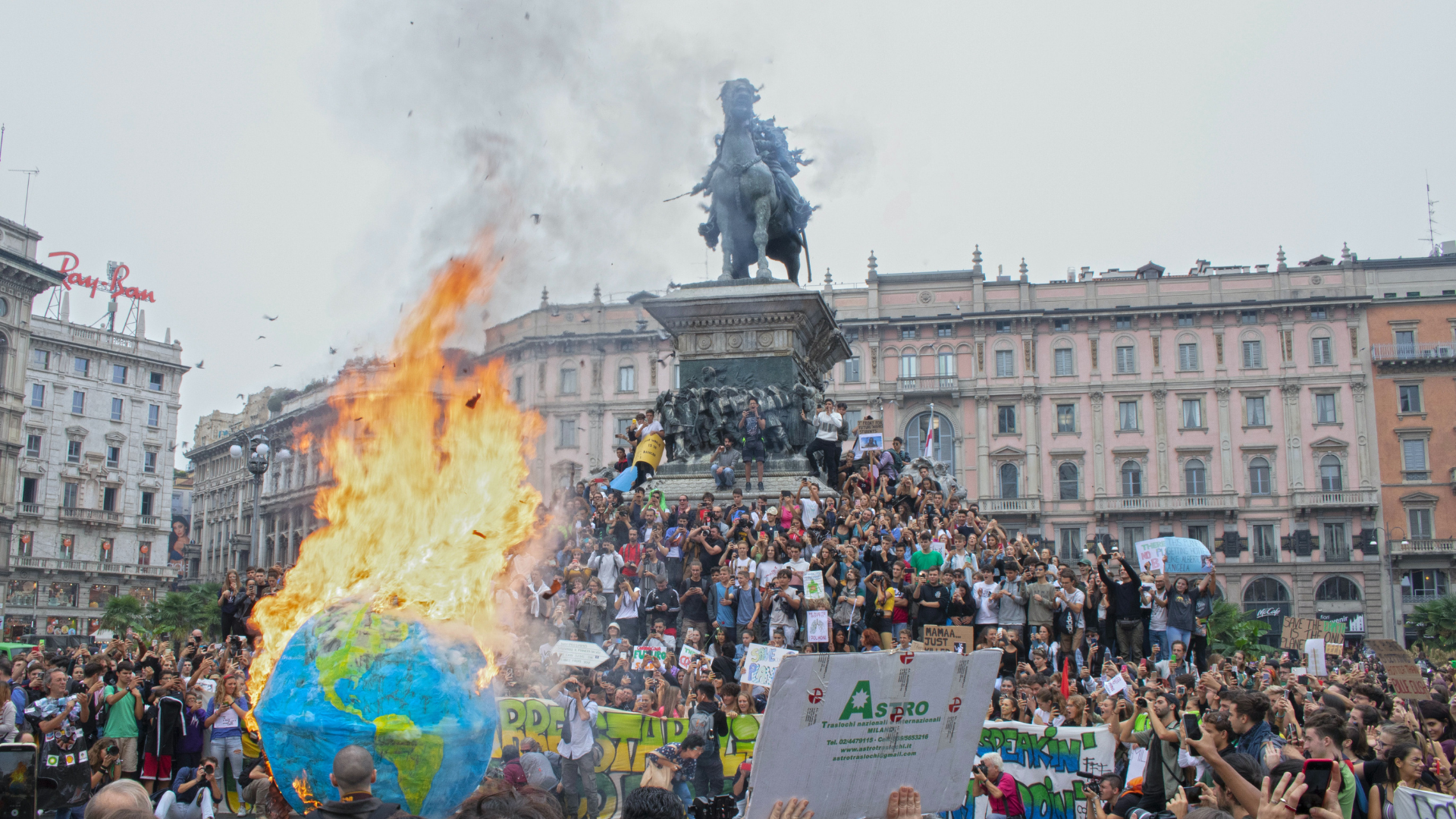people gathered at climate protest with globe on fire
