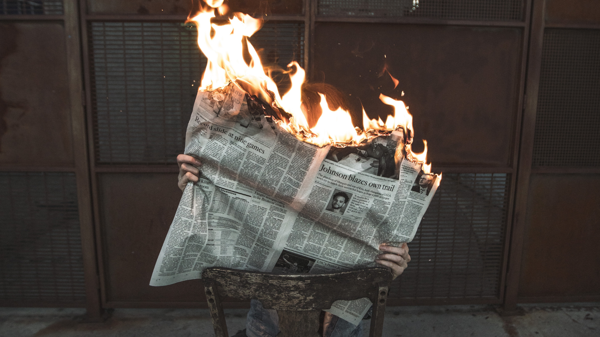 person holding newspaper on fire