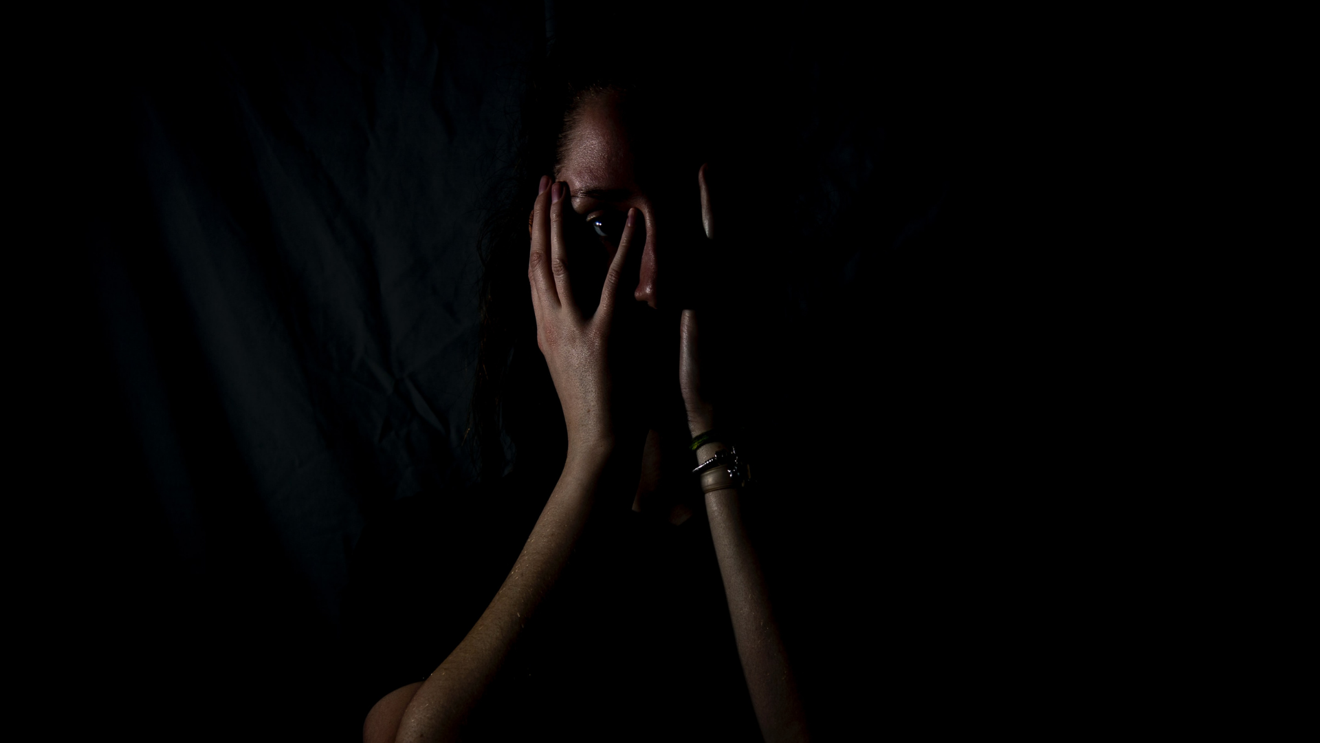 woman in darkness with hands on her face