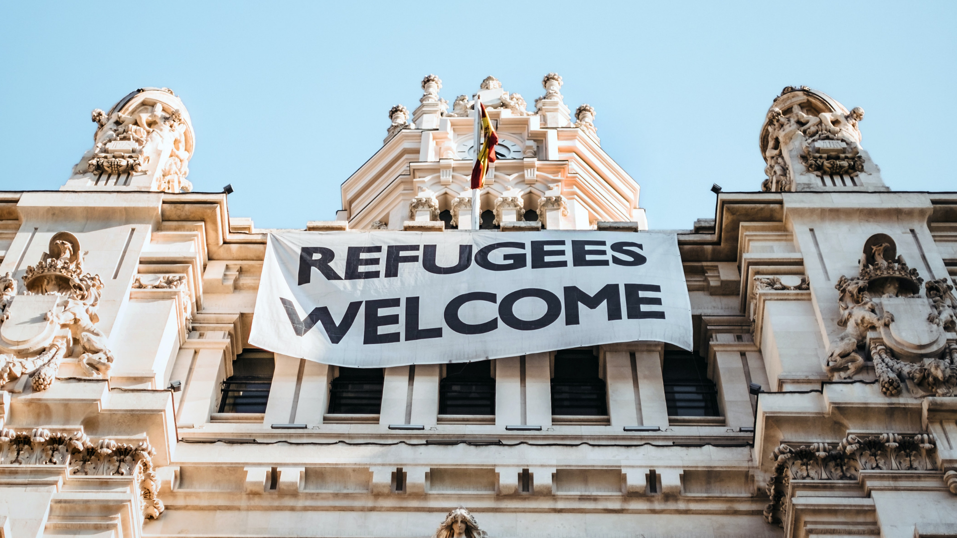 sign draped across a building that reads refugees welcome