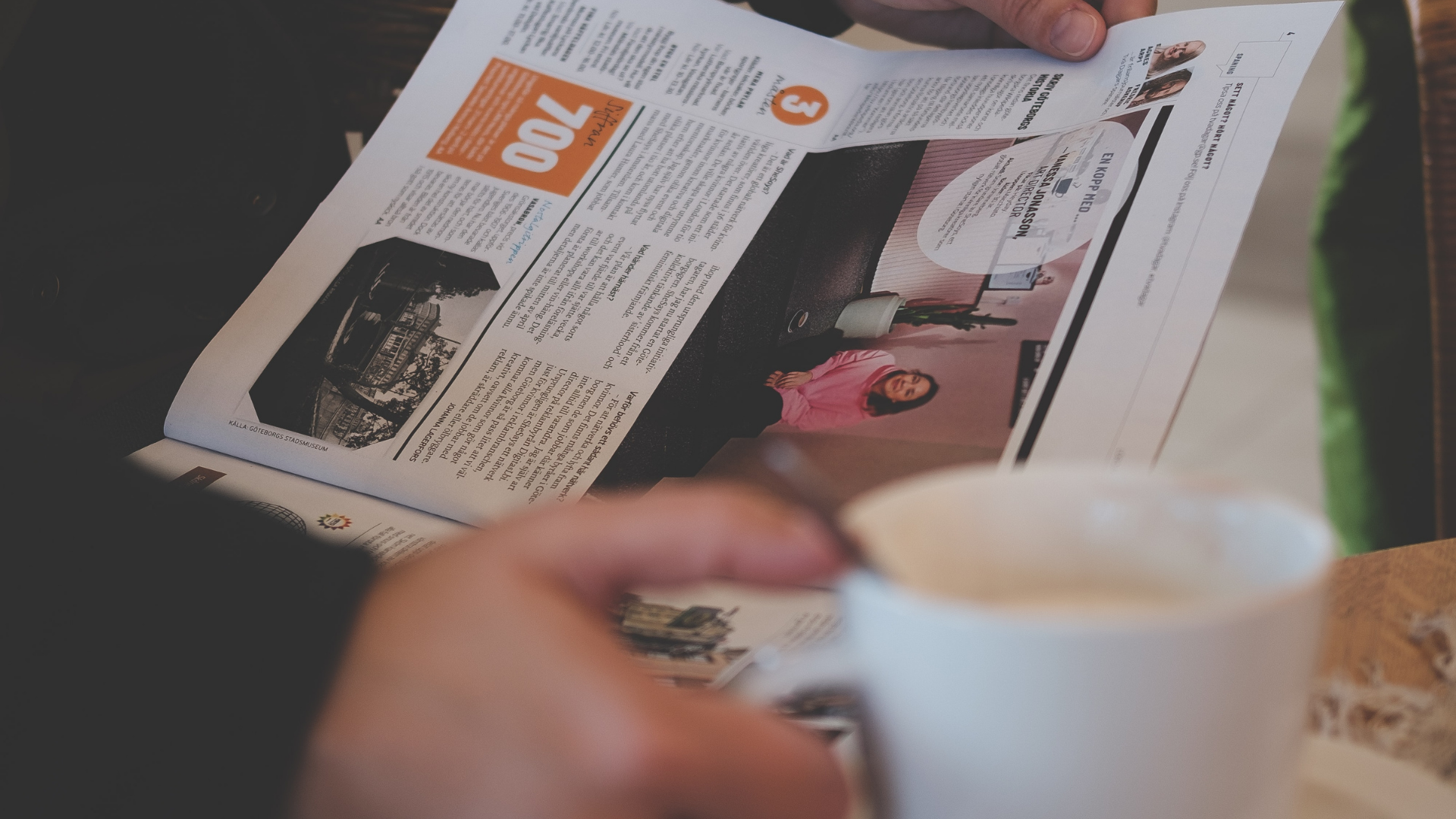 person holding coffee and reading newspaper