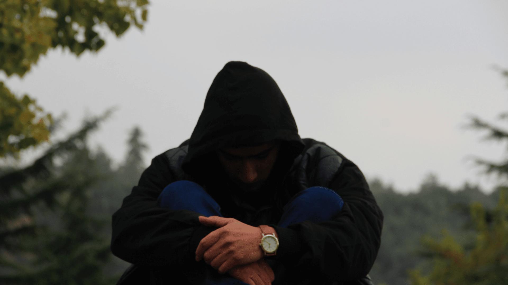 man wearing black hood with head down