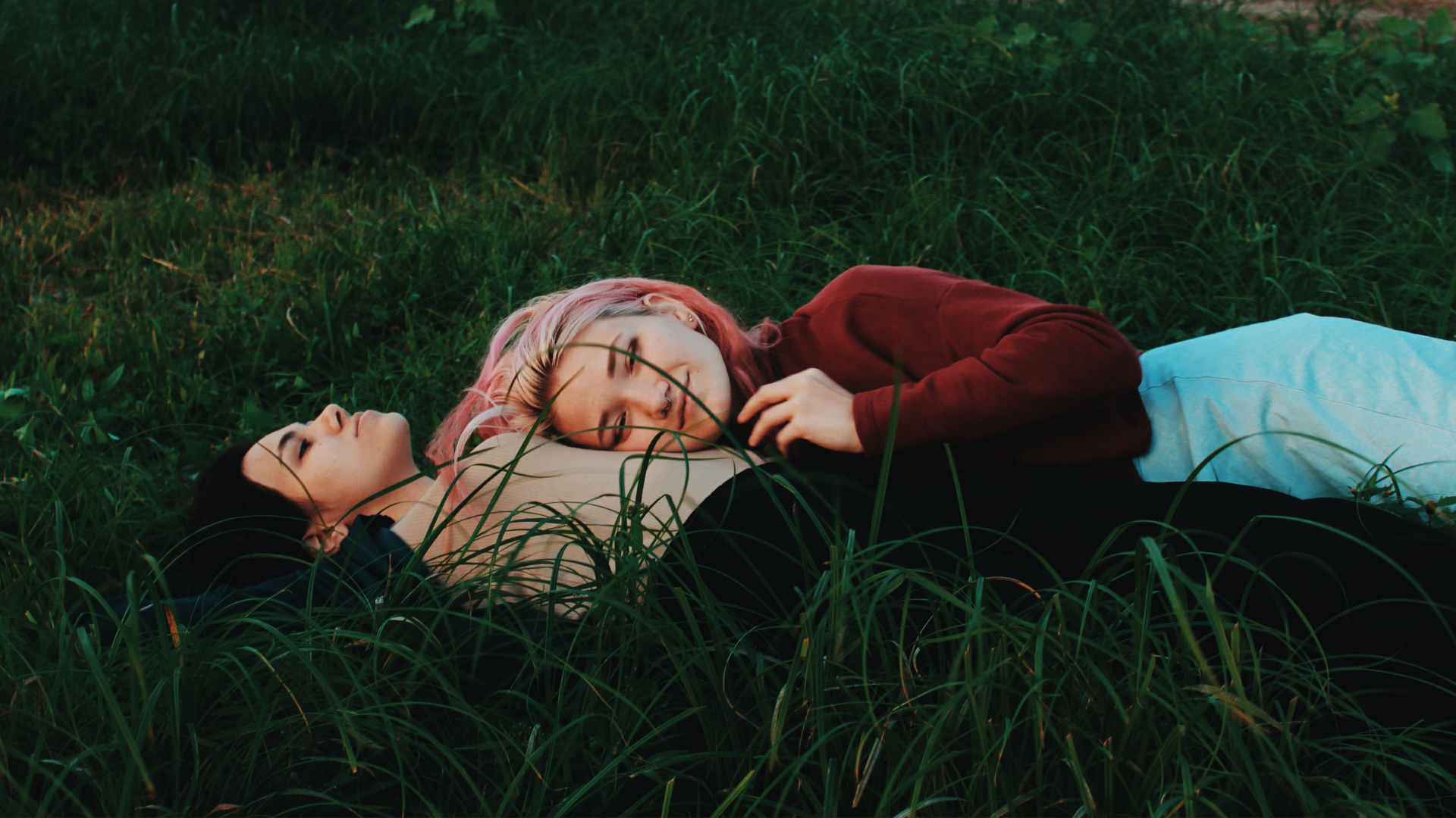 two women cuddle on grass