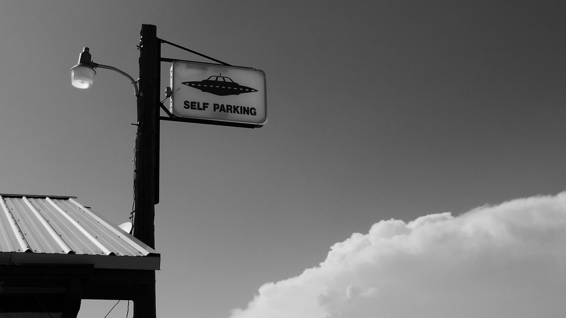 sign with a picture of ufo that says self parking