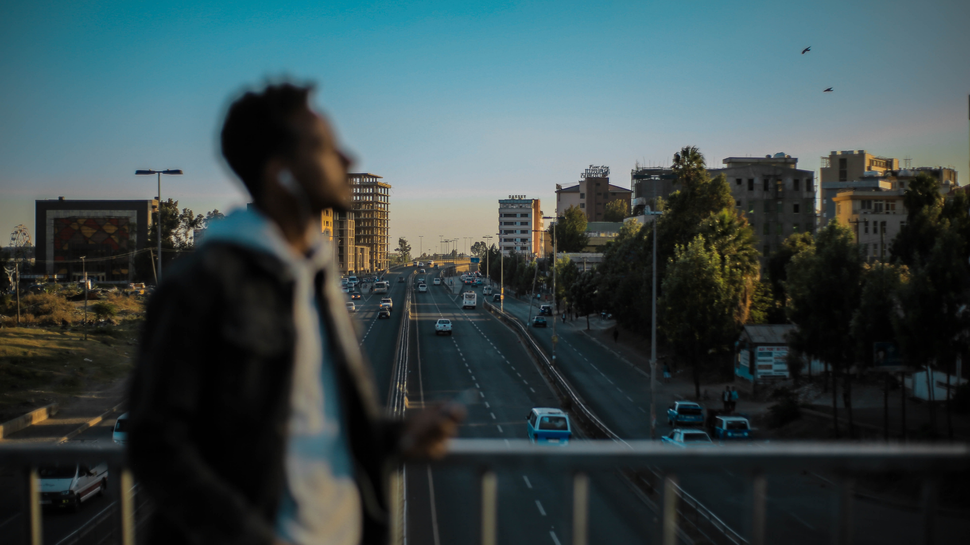 man stands on a bridge above an ethiopian highway